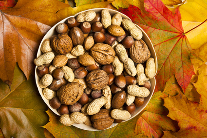 various kinds of nuts - dried fruit - over wooden background with autumn leaves